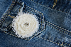 Ivory flower brooch on denim background Stock Photography