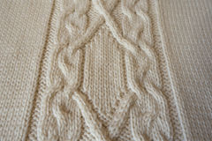 Ivory handmade knitted fabric with plait pattern. Ivory hand made knitted fabric with plait pattern Stock Photos
