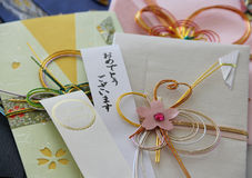 Happy Wedding Japanese Money Envelope. An ivory embellished Japanese money envelope with strips of paper saying Happy Wedding and Omedetou gozaimasu ( Royalty Free Stock Photos