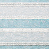 Ivory lace fabric on blue background Stock Image