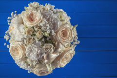 Ivory wedding bouquet of roses on blue wooden background, floral arrangement in pastel colour, celebration Royalty Free Stock Images