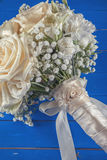 Ivory wedding bouquet of roses on blue wooden background, floral arrangement in pastel colour, celebration Royalty Free Stock Image