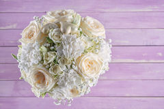 Ivory wedding bouquet of roses on pink wooden background, floral arrangement in pastel colour, celebration Royalty Free Stock Photos