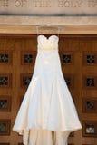 Ivory Wedding Dress. Ivory satin Wedding Dress Hanging on Church Royalty Free Stock Image