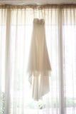 Ivory Wedding Dress. Hanging on window Royalty Free Stock Photography