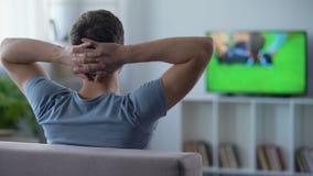 Ivrig fotbollsfan som håller ögonen på nervöst halv-finaler, slut av första halvlek, baksidasikt lager videofilmer