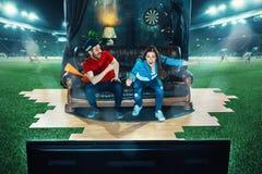 Ivriga fans sitter på soffan och den hållande ögonen på TV:N i mitt av ett fotbollfält Royaltyfria Foton
