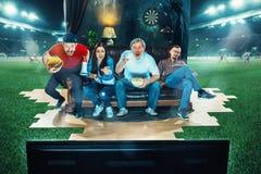 Ivriga fans sitter på soffan och den hållande ögonen på TV:N i mitt av ett fotbollfält Royaltyfri Bild