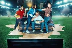 Ivriga fans sitter på soffan och den hållande ögonen på TV:N i mitt av ett fotbollfält Arkivbilder