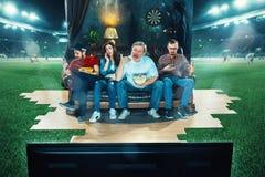Ivriga fans sitter på soffan och den hållande ögonen på TV:N i mitt av ett fotbollfält Arkivfoto