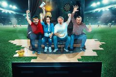 Ivriga fans sitter på soffan och den hållande ögonen på TV:N i mitt av ett fotbollfält Arkivbild