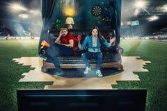 Ivriga fans sitter på soffan och den hållande ögonen på TV:N i mitt av ett fotbollfält Arkivfoton