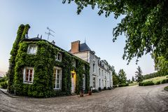 Ivy covered French Chateau in France. An Ivy covered  French Chateau stands under a blue summer sky near Le Mans, June 2015 Stock Photo