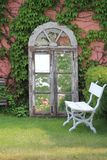 Ivy covered wall with mirror and bench. Ivy coverded wall with a antique mirror leaning against it reflecting garden, White bench alongside hedge and mirror Stock Image