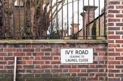Ivy Road Leading a Laurel Close Street Sign contra la pared de ladrillo foto de archivo libre de regalías