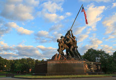 Iwo Jima Marine Memorial Arlington VA. Sunrise casts a warm glow on the figures of the United States Marines in the Iwo Jima Memorial holding an American cloth Royalty Free Stock Photo