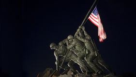 Iwo Jima Memorial at Night. Illuminated statue of Iwo Jima, flag in motion Royalty Free Stock Image