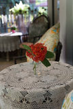 Ixora flower, knitted tablecloth on table, pillow on rattan chai Royalty Free Stock Images