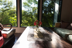 ixora flower, table, chair and sofa in living room near window Stock Photography