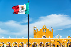 Izamal Monastery and Flag. Yellow colonial monastery in Izamal, Mexico with the Mexican flag flying above royalty free stock photo