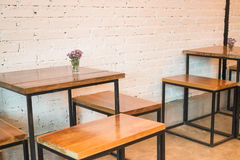 Izbowy wewnętrzny biały ściana z cegieł z drewnianym stołem Obrazy Stock