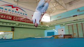 IZHEVSK, RUSSIA - MART 2014: Acrobat man practicing his skills at the gym. IZHEVSK, RUSSIA - MART 2014: Aerial view of gymnast extremely Jumping front flip from stock video footage