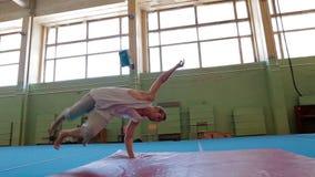 IZHEVSK, RUSSIA - MART 2014: Gymnast doing difficult stunts. IZHEVSK, RUSSIA - MART 2014: Three Axis Gimbal stabilized Gymnast doing difficult stunts. Acrobat stock video footage
