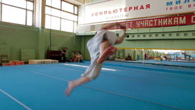 IZHEVSK, RUSSIA - MART 2014: gymnast practicing his skills at the gym. IZHEVSK, RUSSIA - MART 2014: Aerial view of gymnast extremely Jumping front flip from the stock video