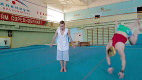 IZHEVSK, RUSSIA - MART 2014: Long shot pan of Gymnasts doing difficult stunts. Acrobat man practicing his skills at the gym stock video