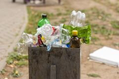 28.07.2021-Izhevsk, Russia.The trash bin is overflowing with various garbage.Empty plastic bottles and packs in a trash can in a