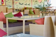 Interior of a restaurant outdoors with tables, sofas and colorful pillows