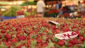 IZMIR - EM JULHO DE 2015: Morangos frescas no mercado no bazar o mais grande e o mais aglomerado em Izmir - Turquia filme