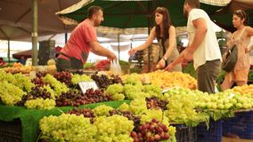 IZMIR - JULY 2015: Customers buying grapes from seller at the biggest and most crowded bazaar in the city. Located in Bostanli, Ka stock video