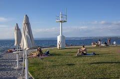 Izola/SLOVENI? - Juni 23, 2018: Mensen die van grote de zomerdag op steenstrand genieten Jongen die handstand voor vuurtoren doen royalty-vrije stock foto's
