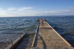 Izola/SLOVENI? - Juni 23, 2018: Mensen die van grote de zomerdag op steenstrand genieten Jongen die op houten pijler lopen stock afbeeldingen