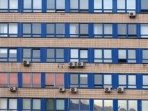 Izoluje z wiele okno miasta budynkiem biurowym: błękitne nadokienne ramy, świeceń okno, klimatyzujący zależący od, życie w dużym  Fotografia Royalty Free
