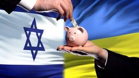 Izrael inwestycja w Ukraina, ręki kładzenia pieniądze w piggybank na chorągwianym tle fotografia royalty free