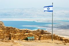 Izraelita flaga z ruinami na Masada z Nieżywym morzem na b obrazy royalty free