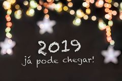 Portuguese phrase about New Years Eve in a black background with blurred lights stock image