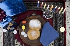 Jánuca Menorah con las velas, los regalos, Dreidel y Jelly Fill encendidos imagen de archivo