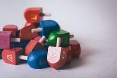 Jánuca: Pila de juguetes de Dreidel en fondo texturizado blanco Fotos de archivo libres de regalías
