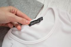 JÁRKOV, UCRANIA - 11 DE AGOSTO DE 2017: Boohoo ennegrece la etiqueta en la camiseta blanca en una mano femenina Primer Fotografía de archivo libre de regalías