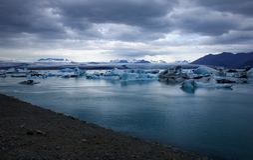 JökulsÃ-¡ rlà ³ n Gletscherlagune unter einem dunklen bewölkten Himmel stockbild