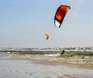 JÃ ¼ rmala Letland Het surfen bij het overzees met een rood valscherm bij s Royalty-vrije Stock Afbeeldingen