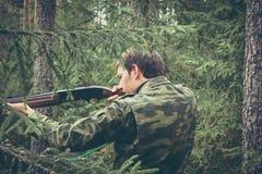 Jägare i skog under jaktsäsongen som siktar för fors arkivbilder