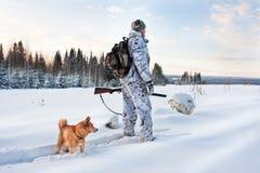 Jägare med hunden på den snöig vägen royaltyfri fotografi