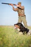 Jägare med hunden som siktar med hans gevär royaltyfria bilder