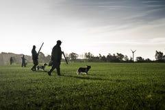 Jägare med jakthundkapplöpning går till och med fält Arkivfoto
