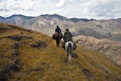 Jägare två hästar gick tillbaka med en trofé efter en jakt Royaltyfri Fotografi