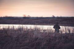 Jägareman i lantligt fält i förväntan av jakt under soluppgång med kopieringsutrymme arkivbilder